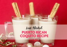 3 cups of coquito on a red background with Christmas ornaments around