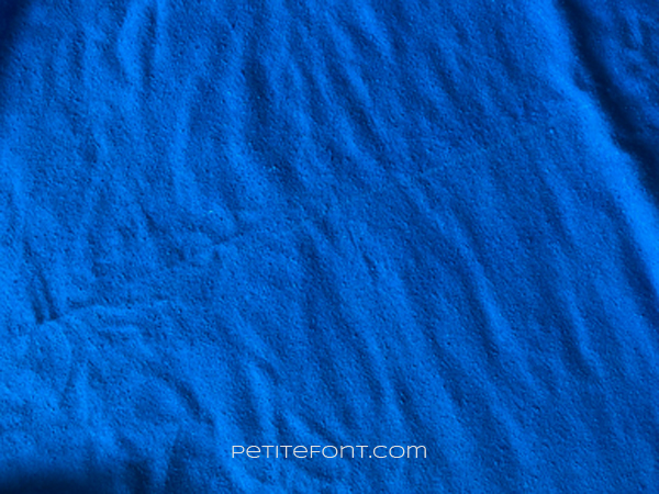 A length of blue silk fabric showing a sun bleached line along the fold