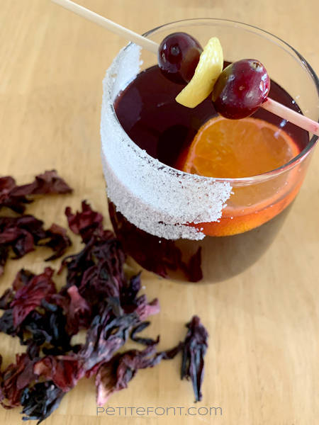 A glass of non-alcoholic mulled wine garnished with cranberries and lemon zest, dried hibiscus flowers scattered about