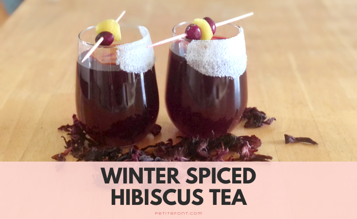 2 glasses of non-alcoholic mulled wine garnished with cranberries and lemon zest, dried hibiscus flowers scattered about. Text overlay reads Winter Spiced Hibiscus Tea