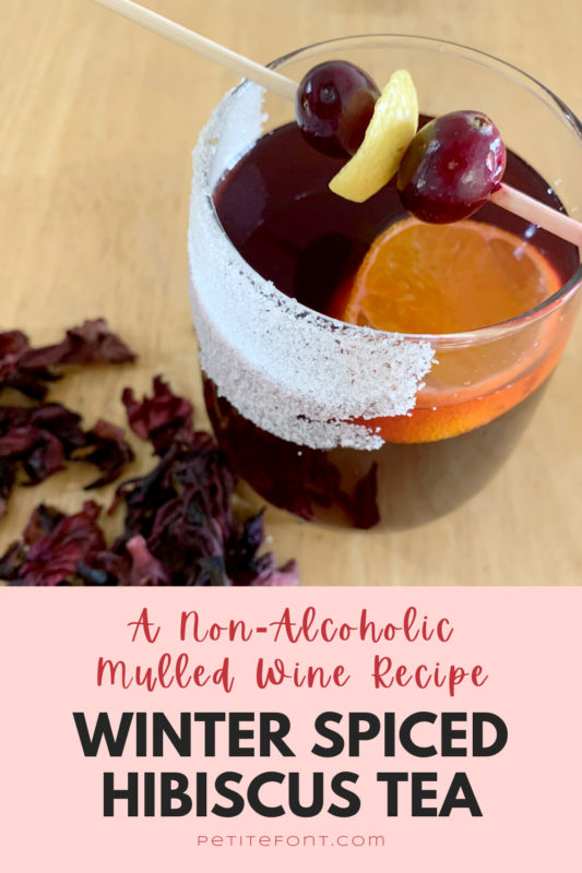 A glass of non-alcoholic mulled wine garnished with cranberries and lemon zest, dried hibiscus flowers scattered about. Text overlay reads A Non-Alcoholic Mulled Wine Recipe: Winter Spiced Hibiscus Tea