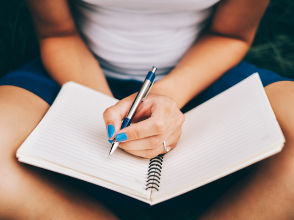 Woman holding open a notebook in her lap, about to start writing probably about her word of the year