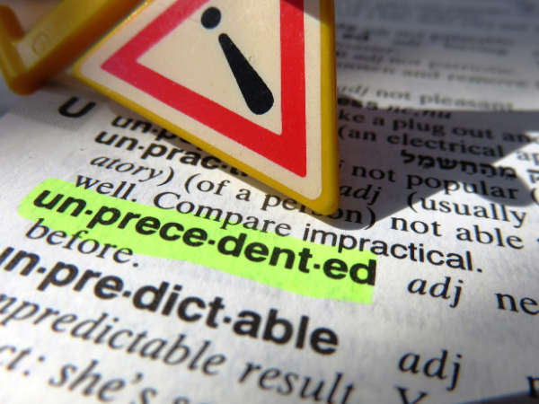 """Close up of a dictionary with the word """"unprecedented"""" highlighted"""