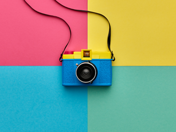 An old school yellow and blue camera with a strap on a background of red, yellow, green, and turquoise rectangles
