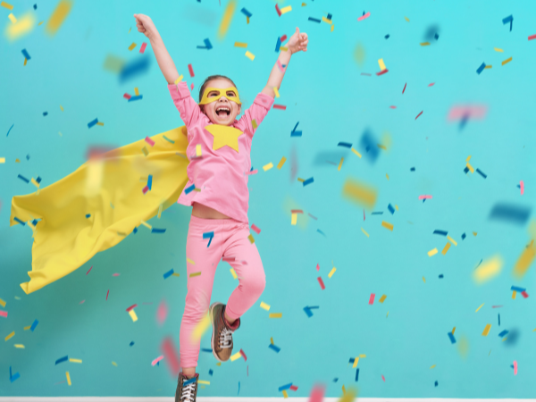 A young girl in a pink track suit with a bright yellow star on her chest and cape and goggles is jumping in the air with her hands up as confetti rains down around her