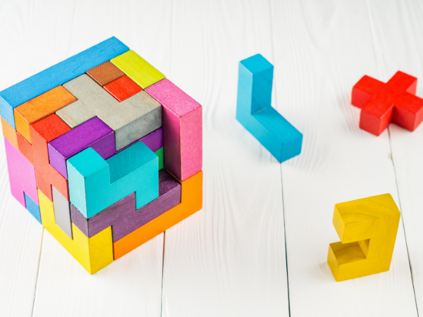 Colorful blocks that form a cube are scattered around a white wood surface