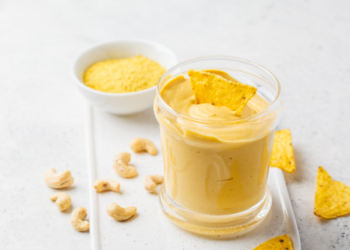 Yellow vegan cheese dip made from cashews with a tortilla chip dipped into