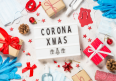 Gifts, holiday twine, masks, and gloves scattered around a lightbox with the words Corona Xmas spelled out