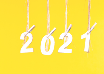 Yellow background with the numbers 2021 hanging from individual pieces of twine