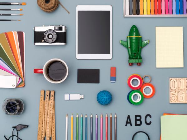Flat lay of various maker tools: a camera, iPad, coffee mug, colored pencils, etc.