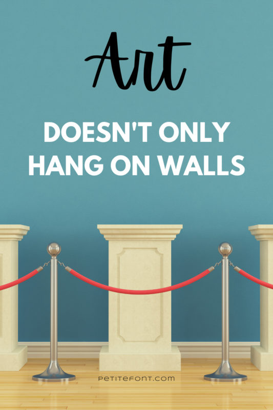 Image of a blue wall with marble pillars behind a red velvet rope. Text overlay reads ART: doesn't only hang on walls