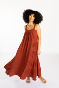 Woman with a beautiful large mane of curls against a white background in a deep amber Marcel tank dress