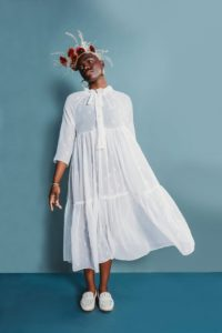 Black model against a blue wall wearing a sheer white version of the Friday Pattern Company Wilder gown, white shoes, and a floral crown