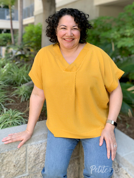 Paulette sitting on a low stone walls in jeans and a bright gold wide v-neck t-shirt